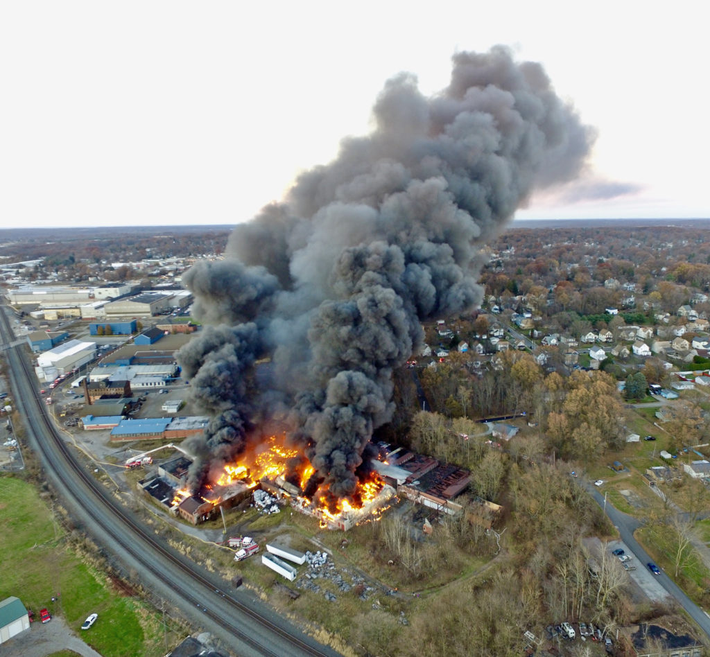 This drone picture courtesy of Jordan Martin shows the scene from the south. A number of fire engines can be seen pouring water on the blaze with the water lines running along the railroad tracks.DCIM100MEDIADJI_0197.JPG
