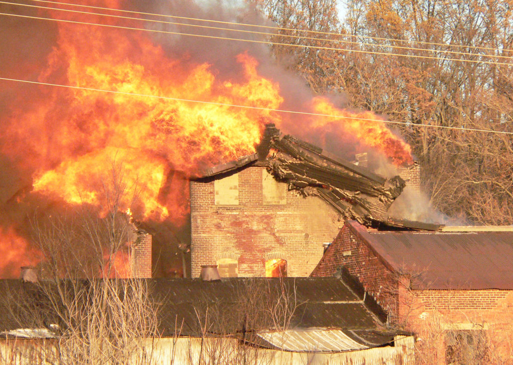 A south wall on the old vacant Salem China building starts collapsing, surrounded by massive flames during a fire which began Tuesday afternoon and stretched well into the night.  Multiple departments responded from all over to battle the blaze. (Salem News photo by Mary Ann Greier)