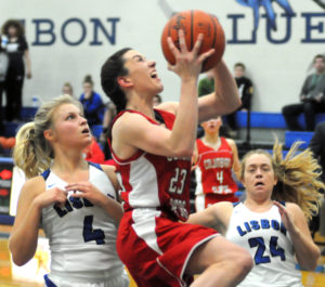 Columbiana's Taylor Hall goes for a layup as Lisbon's Hailee Carpenter (4) and Alyssa Chestnut (24) look on Monday.