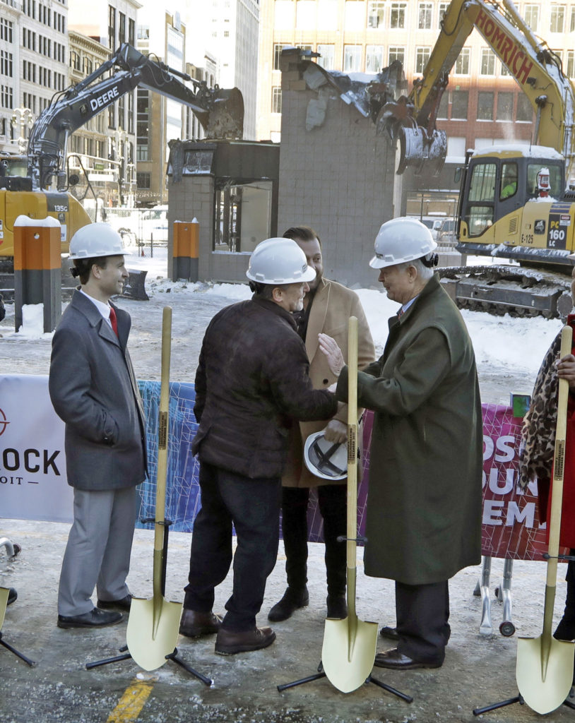Quicken Loans founder Dan Gilbert, center, meets with Joe Hudson, former CEO of the J.L. Hudson Company at the groundbreaking site of the city's new 800-foot-tall building Thursday in Detroit. Bedrock Detroit real estate says the $900 million two-building project will include a 58-story residential tower and 12-floor building for retail and conference space. The tower will have an 800-foot-tall  sky deck.(AP Photo)