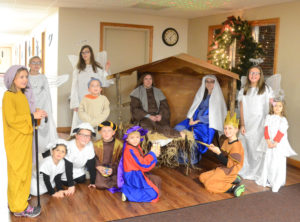 Upon their arrival guests were greeted by the youth of the church presenting a live Nativity scene. Seated from the left are lambs 7-year-old Jenna Postal and 8-year-old Ashlynn Cosma, and wise men 8-year-old Trey Flowers, 10-year-old Micah Cole and 9-year-old Jonathan Postal. In the manager are Jason Cole as Joseph and Erin Postal as Mary.  Standing from the left are shepherd 10-year-old Emily Flowers, angels 11-year-old Aubrey Unkefer and 12-year-old Hannah Cole, shepherd 7-year-old Caleb Cole and angels 11-year-old Savannah Cosma and 5-year-old Abby Cole. The Coles are from Salem, the Cosmas from Boardman and the Postals, Unkefers, and Flowers are from Columbiana. (Salem News photo by Patti Schaeffer)