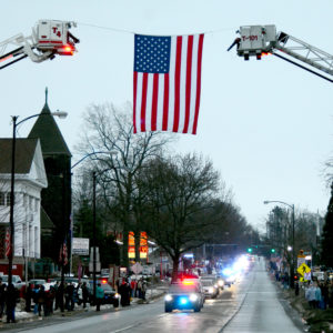 The long funeral processional for Lt. Charles Shafer travels down East State Street in Salem as hundreds of onlookers brave a light rain and cold temperatures Sunday. (Salem News photo by Pattie Shaeffer)