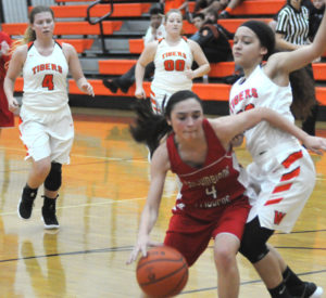 Columbiana's Kayla Muslovski looks to drive past Wellsville's Camryn Jackson during Monday's game. Also pictured Wellsville's Hunter Weekley (left) and Aleia Hawk.