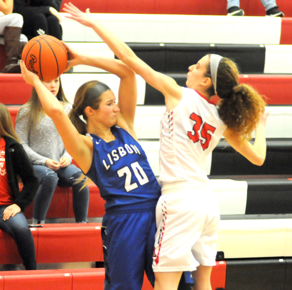 Lisbon's Autumn Oehlstrom looks to pass as Beaver Local's Emily Monte brings pressure during Monday's game.