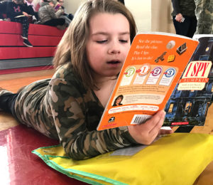 "Second grader Jillina Nagel reads in the gym during ""Stop, Drop and Read."""