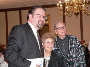 Former Trump White House strategist and frequent FoxNews contributor Dr. Sebastian Gorka, left, poses for a photo with Salem residents Rose and George Corl at the Columbiana County Republican Party Lincoln Day Dinner Monday night at the Timberlanes Complex in Salem. Gorka signed autographs and talked with attendees before delivering the keynote address. (Salem News photo by Mary Ann Greier)