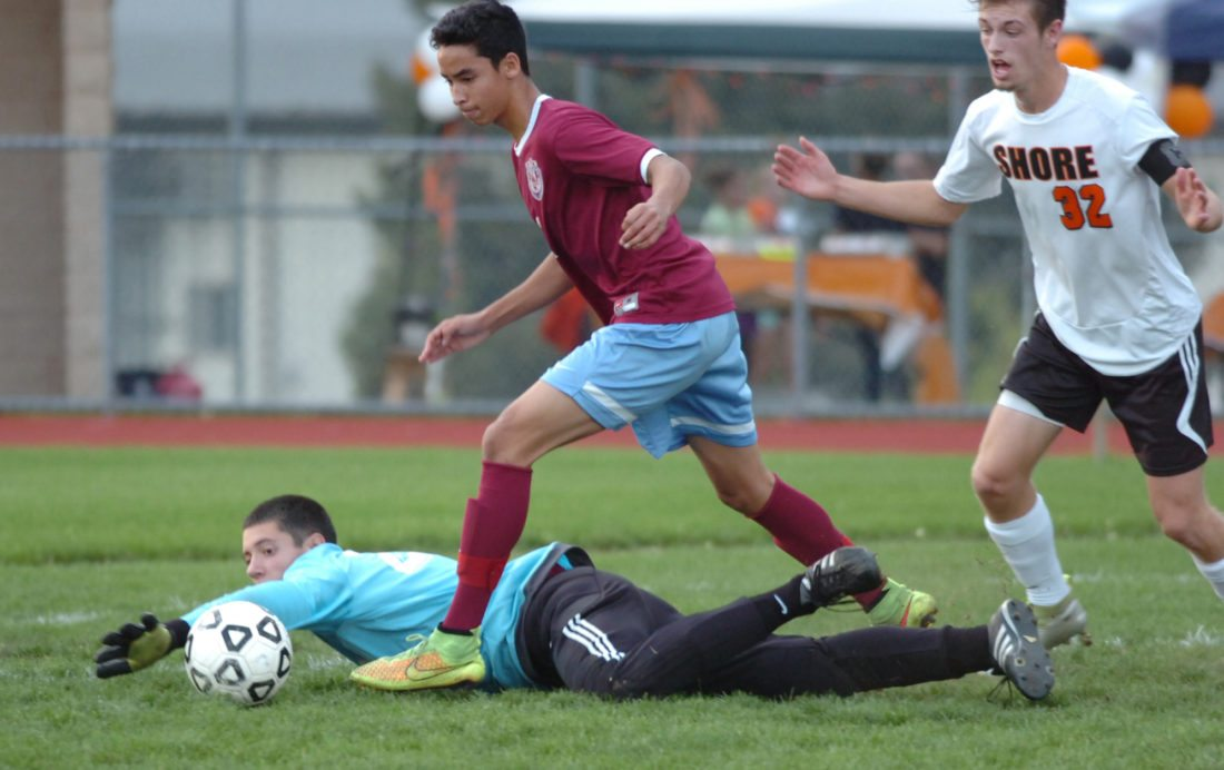 Loyalsock goalkeeper Matt Loeh dives for the ball after colliding with teammate Ilan Quintana and Jersey Shore's Connor Anderson during the first half at Jersey Shore on Thursday. MARK NANCE/Sun-Gazette