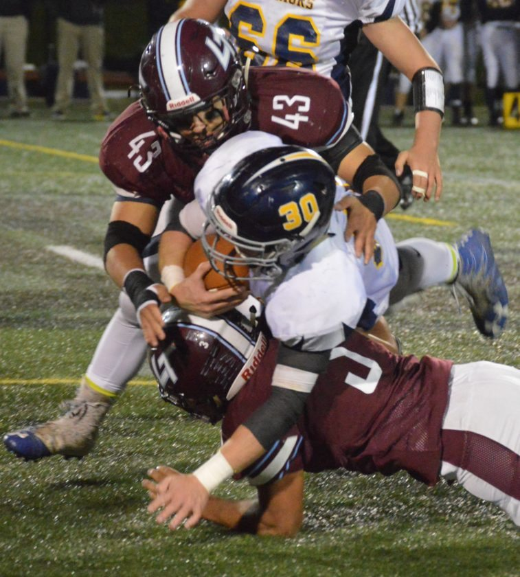 Alden Mileto (43) and Marcus Williams (3) of Loyalsock tackle Nolan Ott (30) of Montoursville Friday night at Loyalsock.