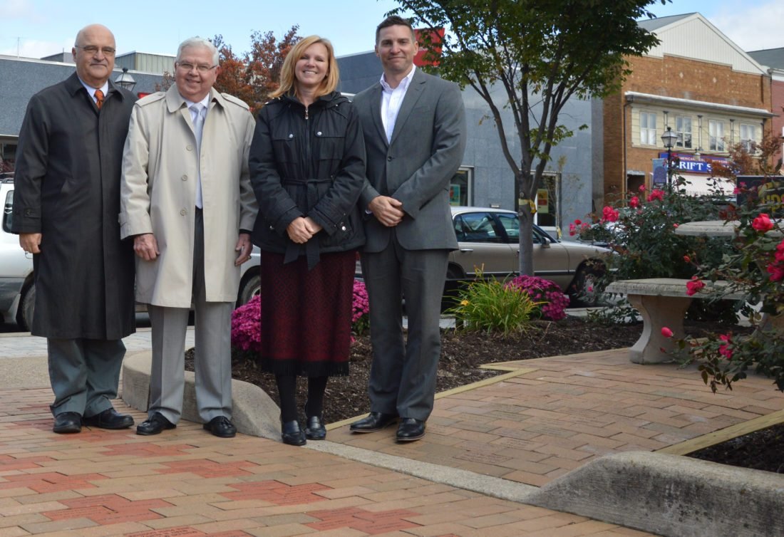 KATELYN HIBBARD/Sun-Gazette Vincent J. Matteo, president and CEO of the Williamsport/Lycoming Chamber of Commerce, Montoursville Mayor John Dorin, Montoursville Chamber Chairwoman Sue Harvey and Vice Chairman Will Daniels pose for a photo on the re-paved patio of the Broad Street Mini-Park.