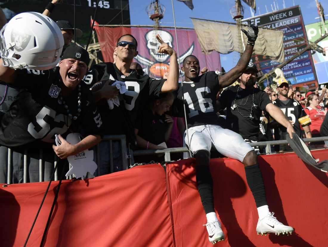Oakland Raiders wide receiver Johnny Holton (16) celebrates with the fans after the Raiders defeated the Tampa Bay Buccaneers 30-24 in overtime of an NFL football game Sunday, Oct. 30, 2016, in Tampa, Fla. (AP Photo/Jason Behnken)