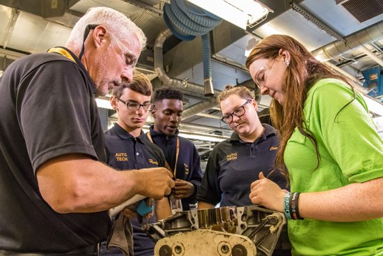 PHOTO PROVIDED Milton Hershey School student Mya Ott, of Williamsport, second from right, developed her interest in mechanics from her first shop class in seventh grade. Ott works on repairing automotive parts with her classmates and teacher.