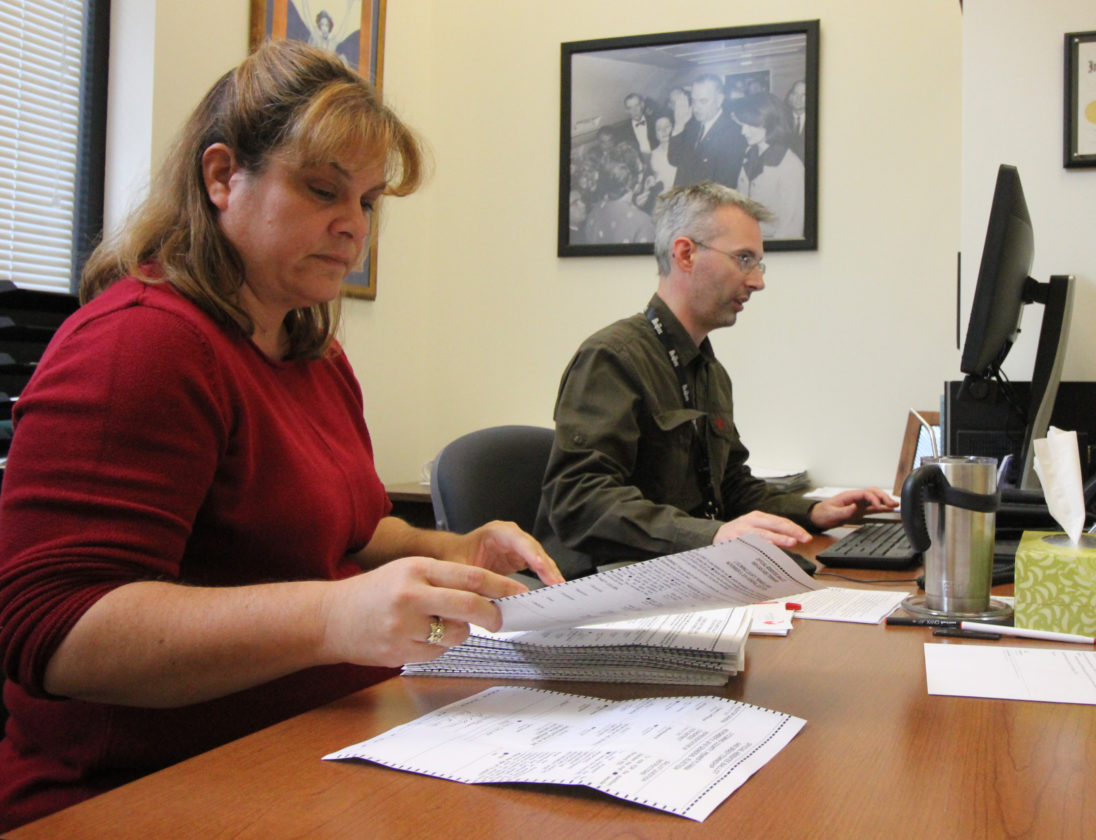 ANNE REINER/Sun-Gazette  Jill Shuman, left, assistant director, and Forrest Lehman, director of Voter Services in Lycoming County, count hand-written absentee ballots at the Voter Services office Friday afternoon.