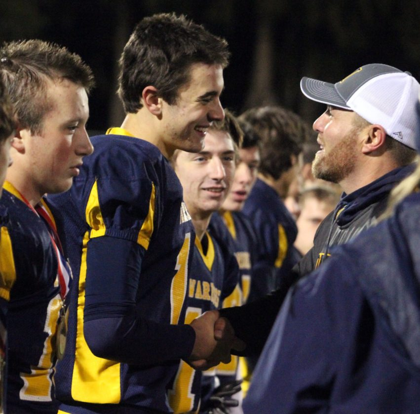 Montoursville coach J.C. Keefer shakes with quarterback Brycen Mussina during the medal ceremony after beating Danville for the District 4 Class AAA title.