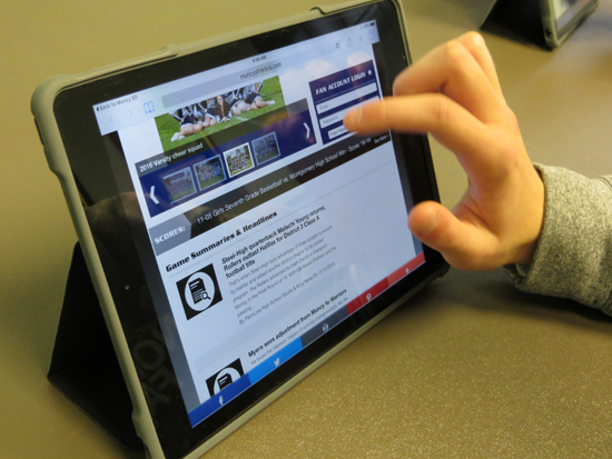 CARA MORNINGSTAR/Sun-Gazette Jacob Hill, ninth grader, looks at the new Muncy School District app on iPads at Muncy Jr. Sr. High School. The app displays photos from sporting events.