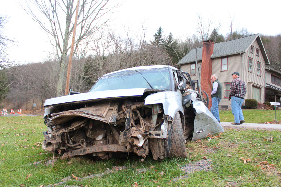 MEGAN E. BLOOM/Sun-Gazette Joe Colucci, emergency management coordinator for Cascade and Gamble townships, gave the Sun-Gazette and state Rep. Garth Everett, R-Muncy, a tour of the areas of his jurisdiction that received severe damage from the October flooding. A resident's car was swept away in the current and was found miles down the creek completely filled with mud. Behind the car are Everett, left, and Colucci, right.