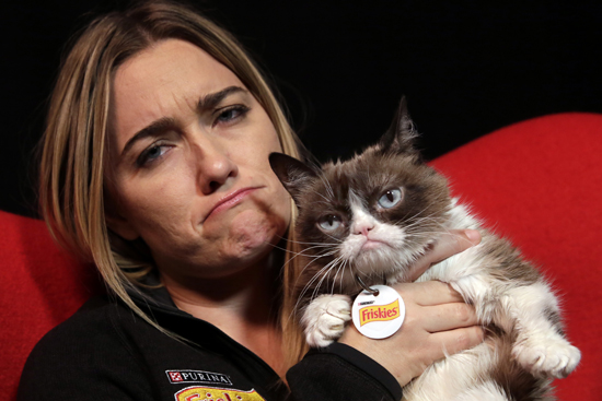 In this Nov. 14, 2016 photo, Grumpy Cat poses for photos with her owner Tabatha Bundesen in New York. The social media star posted her Top 10 pet peeves on her new blog at Pawculture.com. (AP Photo/Richard Drew)