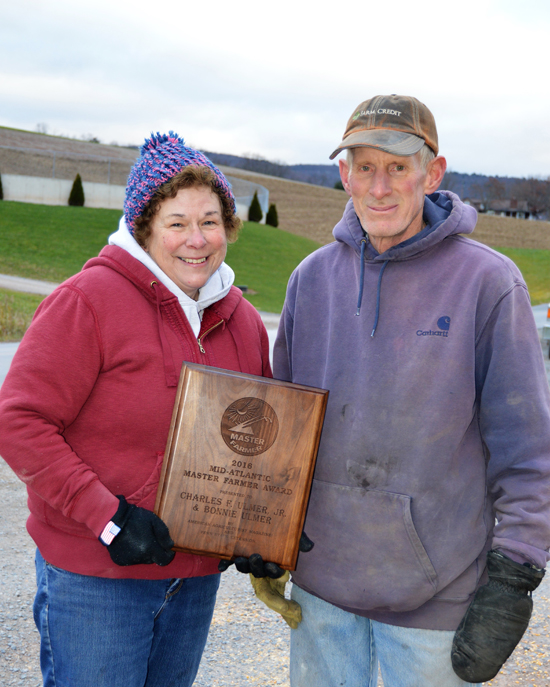 PAT CROSSLEY/Sun-Gazette Correspondent Charles Ulmer Jr. and his wife, Bonnie, hold the plaque they received Aug. 5, along with the title of Master Farmers.