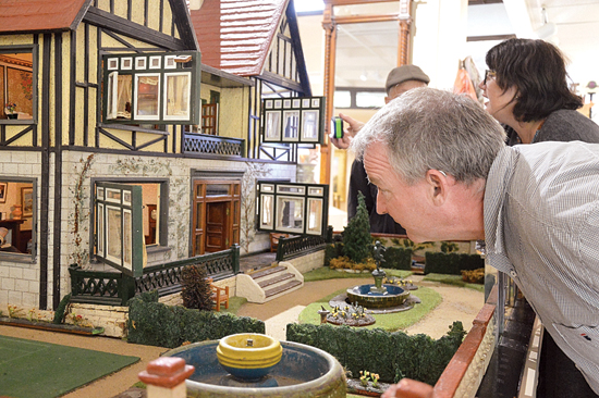 KATELYN HIBBARD/Sun-Gazette Nicholas David Mowbray Finnis and his wife Annette peer into the many rooms of the Manor Hall House dollhouse.
