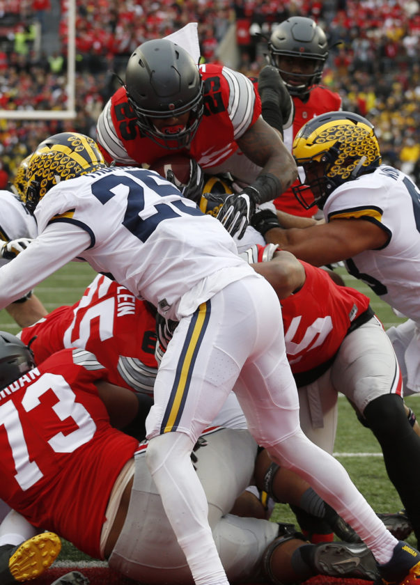 Ohio State running back Mike Weber, top, scores a touchdown against Michigan during the second half of an NCAA college football game Saturday, Nov. 26, 2016, in Columbus, Ohio. Ohio State beat Michigan 30-27 in double overtime. (AP Photo/Jay LaPrete)