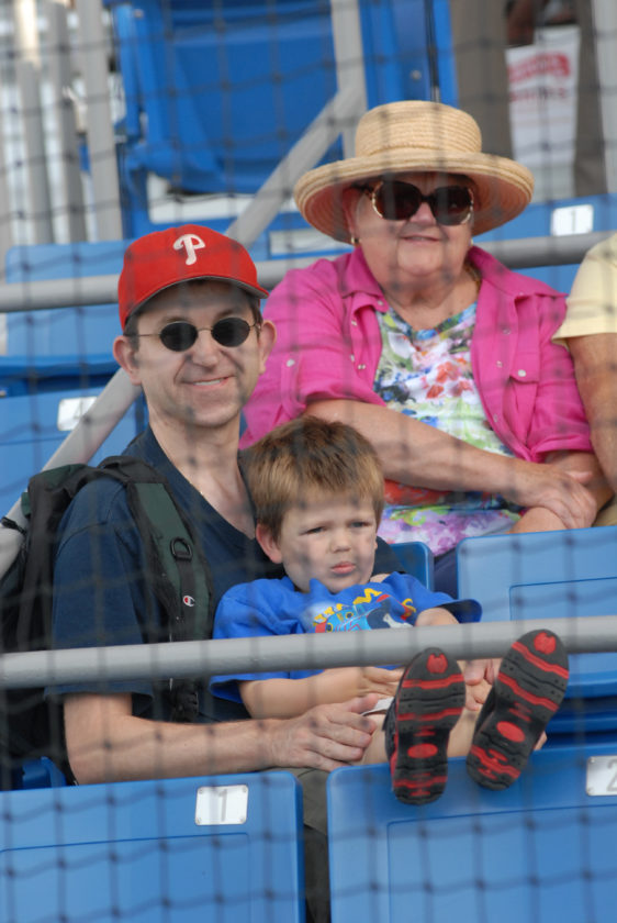 Bowman Field netting protects Grahm family members from left, Jove, Thomas, and Tobi during a Crosscutters game.