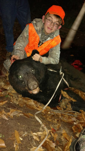 """PHOTOS PROVIDED Charlie Pittenger, 15, of New Columbia, shows off his first black bear, which he shot on the first day of rifle deer season last month. When he and his dad headed into the woods that day, Charlie was hoping to bag his first buck. Harvesting the bear instead still """"was a special thing,"""" Charlie said, even though the meat was inedible due to an infection."""