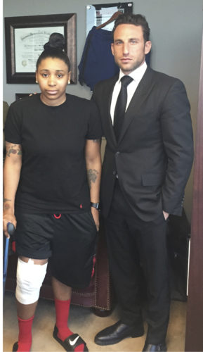 In this April 2016 photo provided by Lipsig, Shapey, Manus & Moverman P.C., Marc Eli Freund stands with client Katrina Williams at the law firm's offices in New York, as she recovers from injuries she says she got from an exploding e-cigarette.       ASSOCIATED PRESS