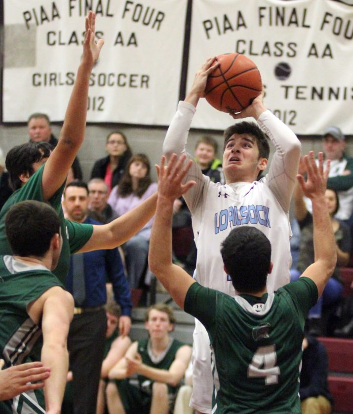 Loyalsock's Anthony Pastore shoots around the defending Hughesville players during the game Friday night in Loyalsock.