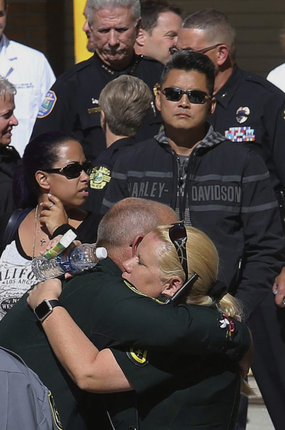 ASSOCIATED PRESS Friends and colleagues console each other after the body of Orange County Sheriff's Office Deputy First Class Norman Lewis was transported from Orlando Regional Medical Center after the deputy was killed in the line of duty in Orlando, Fla., Monday. An Orlando police sergeant was shot and killed Monday after approaching a suspect wanted for questioning in the murder of his pregnant ex-girlfriend, and Lewis was killed in a crash while responding to a manhunt for the suspect.