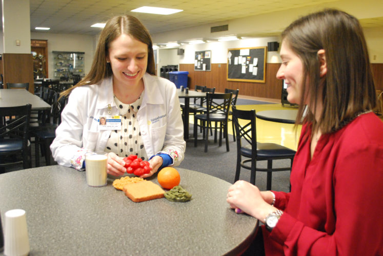UPMC Susquehanna dietitian April Mase, left, consults with a patient at Williamsport Regional Medical Center. Mase says healthful eating choices can make for a better year, year after year.       PHOTO PROVIDED