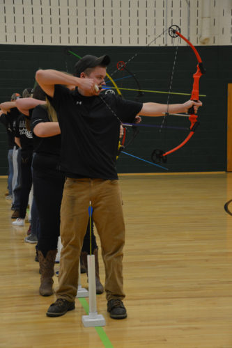 KATELYN HIBBARD/Sun-Gazette Archers from Halifax High School line up for a practice end during a recent National Archery in the Schools Program state qualifier at Ashkar Elementary School.