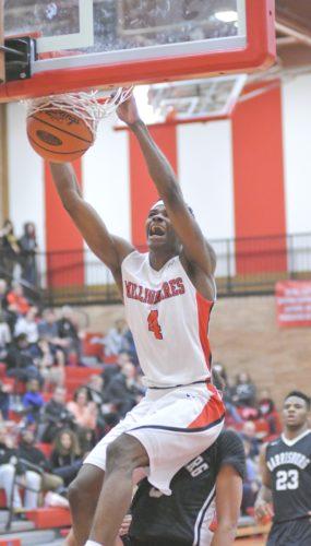 Stanley Scott of Williamsport dunks over Elijah Barrett Thursday at Williamsport. (MARK NANCE/Sun-Gazette)