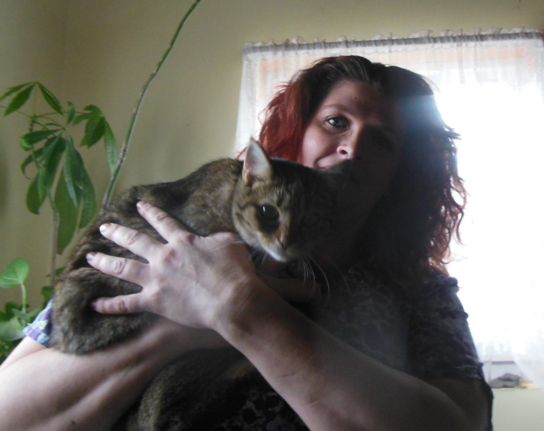 MIKE REUTHER/Sun-Gazette Amie Palmer, who recently started a pet-sitting business, holds her cat.
