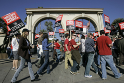 FILE - In this Dec. 13, 2007, file photo, striking writers walk the picket line outside Paramount Studiosin Los Angeles. The clock is ticking on negotiations between television and film writers and producers before their contract expires. A strike could begin Tuesday, May 2, 2017, forcing writers to begin picketing. The previous writers' strike lasted 100 days in 2007-08 and was costly to the businesses that serve Hollywood and to consumers expecting to be entertained. (AP Photo/Nick Ut, File)