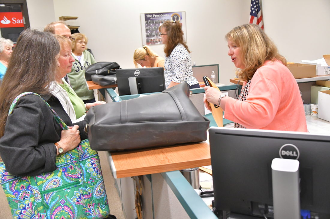 MARK NANCE/Sun-Gazette Mary-Kay Camp, of Lycoming County Voter Services, right, takes election packets from different precincts at the Voter Services office Tuesday night.