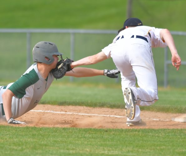 MARK NANCE/Sun-Gazette Hughesville's Zack Murray is tagged out by Montoursville first baseman Mitchell Rothrock as he dives back to the bag on a fly ball in the fourth inning Tuesday at Montoursville.