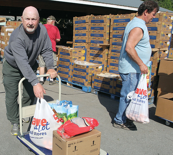 KAREN VIBERT-KENNEDY/Sun-Gazette VFW member John Kropp pushes a cart full of food toward a waiting car during last week's food distribution for veterans at the VFW in DuBoistown.