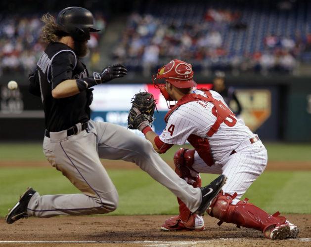 The Colorado Rockies' Charlie Blackmon, left, scores past Philadelphia Phillies catcher Andrew Knapp on a single by Nolan Arenado during the third inning on Wednesday in Philadelphia. (AP)