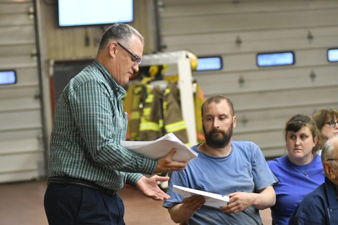 MARK NANCE/Sun-Gazette Charles Hall, legislative aide for state Rep. Garth Everett, R-Muncy, hands out copies of the state budget information  during a town hall meeting at the Unityville Volunteer Fire Co. Thursday.