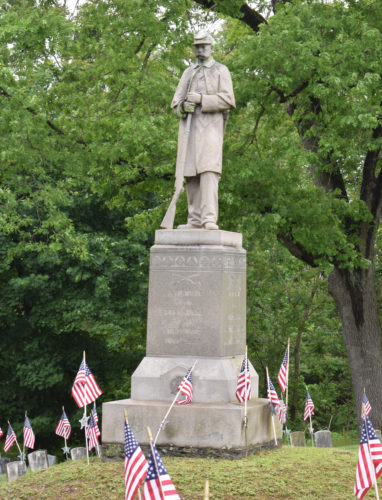 "IOANNIS PASHAKIS/Sun-Gazette  Flags decorating The Civil War memorial at Wildwood Cemetery surround the statue at the middle of the memorial, the ""Soldier at Rest."""