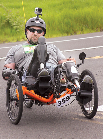 BRAD MOSHER/Tillamook Headlight Herald Wade Mitcheltree, above, a former Army infantryman from Williamsport who was wounded in Afghanistan, climbs the hill on his recumbent bicycle while participating in a 28-mile leg of the Reach the Beach fundraiser in Oregon, where Mitcheltree now lives. His father Randy Mitcheltree traveled from Williamsport to ride alongside his son in the event that raised $750,000 for the American Lung Association.
