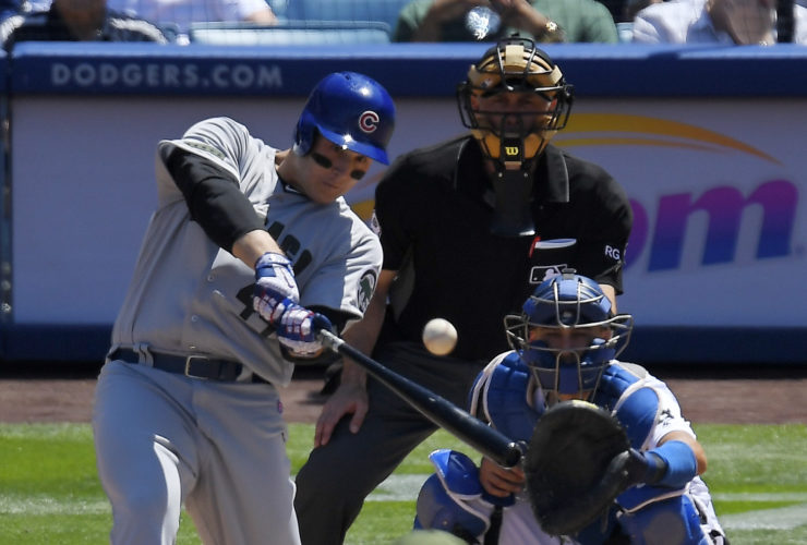 The Chicago Cubs' Anthony Rizzo, left, hits a three-run home run as Los Angeles Dodgers catcher Austin Barnes, right, watches along with home plate umpire Dan Iassogna during the fourth inning on Sunday in Los Angeles. (AP)