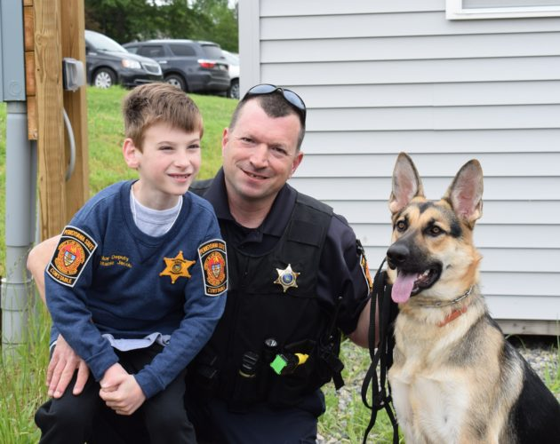 IOANNIS PASHAKIS/Sun-Gazette  Loyalsock Township Constable Steven Bowman present Jacob Stopper with the title of Junior Deputy Constable along with an honorary sweater, with help from his German shepherd, Maisy.