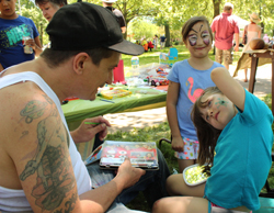 CARA MORNINGSTAR/Sun-Gazette Levi Wifthoft, left, helps Olivia Brundage, 5, pick a face painting design as her sister, Sophia Brundage, 7, stands by during the Way's Garden Art Show in Williamsport on Sunday.