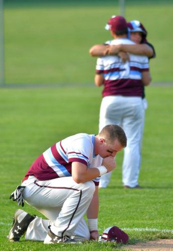 MARK NANCE/Sun-Gazette Loyalsock's Andrew Malone pauses at third base as Derek Gee and another player hug in the outfield after their 4-0 loss to Holy Redeemer for the PIAA Class AAA semi-final game at Central Columbia Monday.