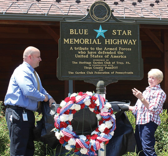 CARA MORNINGSTAR/Sun-Gazette Mark Verrico, Tioga County manager for Pennsylvania Department of Transportation, and Sharon Brown, past president of the Garden Club Federation of Pennsylvania, unveil the Blue Star during the Blue Star Memorial Highway Dedication Marker Dedication at the Route 15 Welcome Center in Tioga on Wednesday.