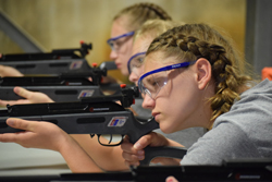 IOANNIS PASHAKIS/Sun-Gazette From left to right, Kamryn Pryer, Abbigail Davis and Kerryn Best shoot BB guns at a bundle of hay bailes as part of Camp Cadet's firearm safety portion of the week.