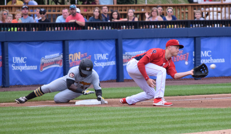 West Virginia's Huascar Fuentes steals third base as the Williamsport Crosscutters' Cole Stobbe tries to field the throw at Bowman Field on Thursday. (IOANNIS PASHAKIS/Sun-Gazette)