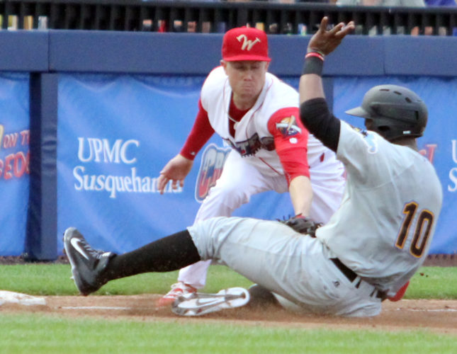 The West Virginia Black Bears' Julio De La Cruz is tagged out as he slides into third base by the Williamsport Crosscutters' Cole Stobbe on Friday night at Bowman Field. (KAREN VIBERT-KENNEDY/Sun-Gazette)