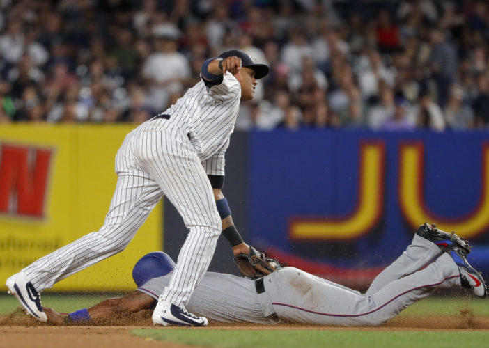 New York Yankees second baseman Starlin Castro tags out Texas Rangers' Elvis Andrus as he attempts to steal second base during the first inning of a baseball game, Friday, June 23, 2017, in New York. (AP Photo/Julie Jacobson)