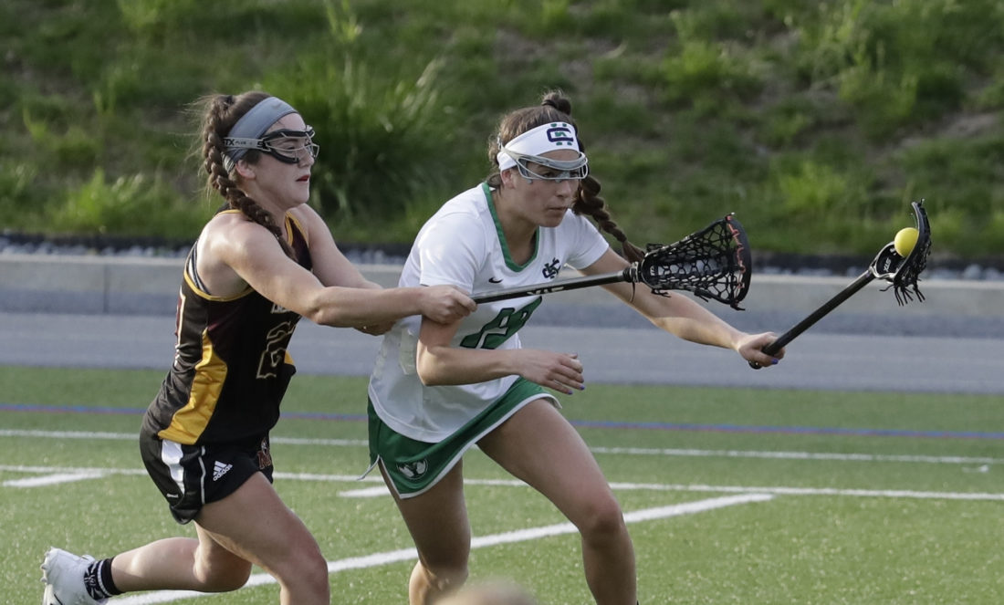 In this May, 3, 2017 photo, Mercy's Libby Bartels, left, reaches in on Cranbrook Kingswood's Angelina Wiater during a lacrosse game at Cranbrook Kingswood School in Bloomfield Hills, Mich. Helmets are not a required piece of equipment worn by female high school lacrosse players. And this year, the National Federation of State High School Associations allowed the optional use of two models of headgear beyond the previously allowed padded headbands. (AP)